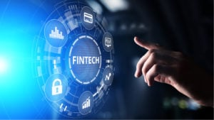 """A concept image of a hand reaching toward the word """"Fintech,"""" which is surrounded by icons representing money and growth."""